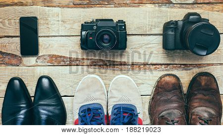 Three pairs of shoes and three camera. Busines shoes casual shoes hiking boots on wooden backgriound Concept of choosing right footwear