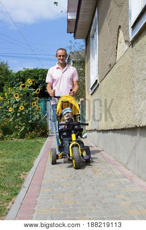 father his son to ride a tricycle on the pavement