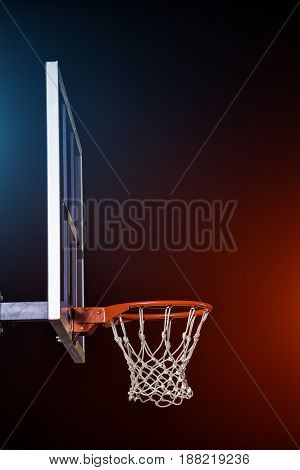 Basketball hoop isolated on black background. Lightened by mixed color lights.