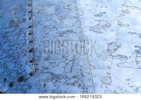 Sanded steel surface with rivets blue color prepared for paint close-up view