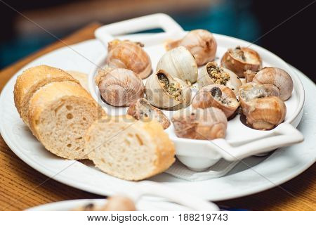 Snails with herbs butter, in traditional ceramic pan with cut parsley, bread and and parsley sauce on textile napkin over rustic wooden table. Top view. restaurant food and wine tasting