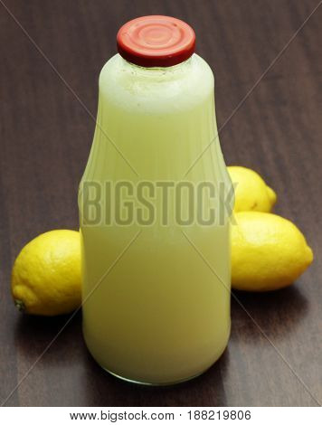 Lemon Remedy in Glass Bottle on Wooden Table
