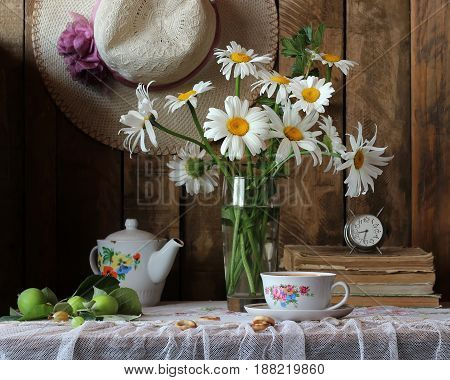 Country still life with a bouquet of fresh flowers retro Cup alarm clock and unripe apples.