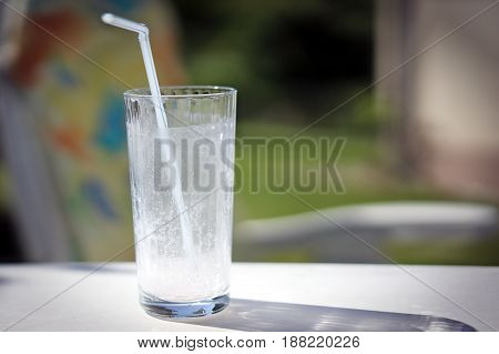Empty glass from a milk cocktail with a straw on a garden table