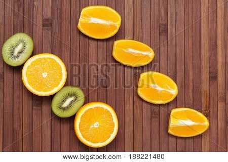 Fresh fruits kiwi, orange isolated on wooden background. Healthy food. A mix of fresh fruit. Group of citrus fruits. Vegetarian raw fruit. Nutrition for a healthy lifestyle.