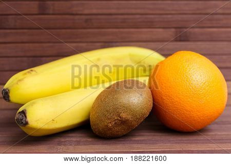 Fresh fruits banana, kiwi, orange isolated on wooden background. Healthy food. A mix of fresh fruit. Group of citrus fruits. Vegetarian raw fruit. Nutrition for a healthy lifestyle.