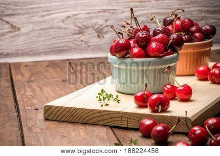 Red Ripe Cherries In Ceramic Bowls