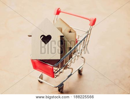 Little houses in shopping cart ,money saving for new houses and family.