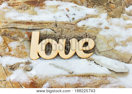 Close-up wooden love sign on stone texture with snow. Love concept
