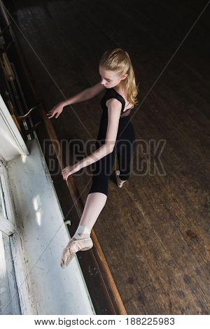 Female ballet dancer stretching at ballet barre. Top shot.