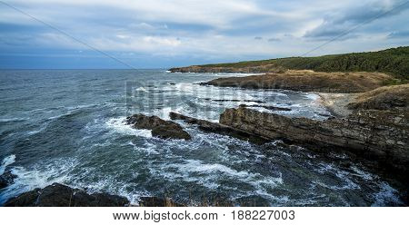 rocky seascape with cloudy sky after storm