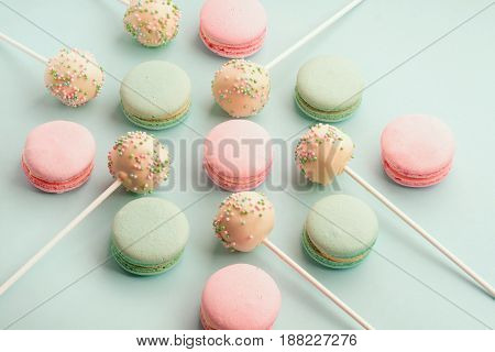 Sweet colorful macaroons with cake pops or cake crumbs with icing on sticks