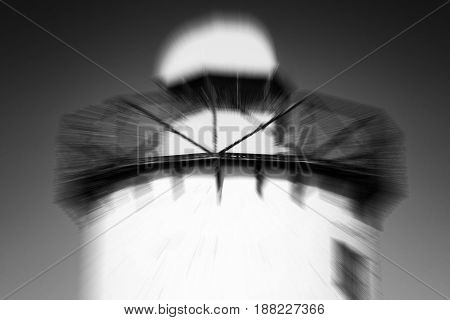 Black and white image of an old 19th century Georgian lighthouse at Burry Port, Carmarthenshire, Wales, UK with a zoom burst blur effect