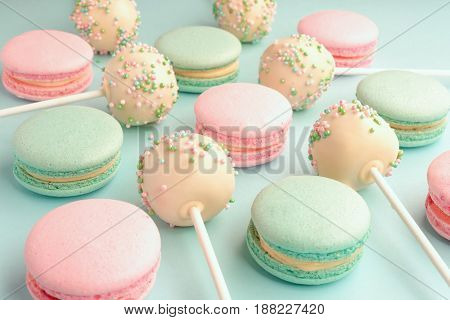 Close-up of colorful sweet macaroons mixed with cake crumbs with icing on sticks on blue background