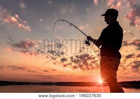 Man fishing on the lake at sunset.