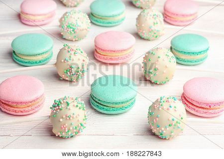 Colorful macaroons mixed with cake pops on sticks on white wooden background