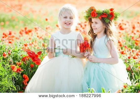 freedom, celebration, dream, happy childhood concept - in the poppy field two giggling girlfriends in white and blue sleeveless dresses holding posies of wild flowers