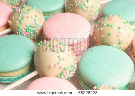 Macro shot of sweet macaroons mixed with cake pops with icing