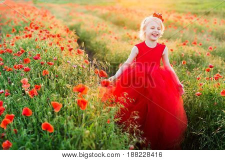 kid fashion, wedding, summer, weekends, flora, freedom concept - sorrounded by poppies little adorable model with flowers in blond hair and in poofy crimson dress laughing