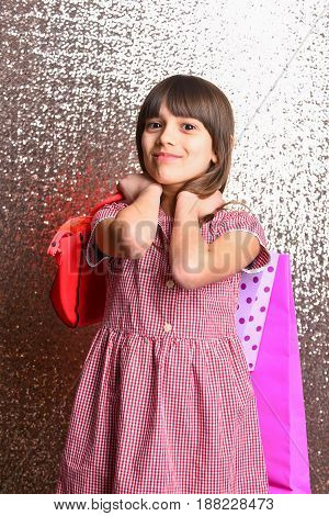 Small Smiling Girl With Red Leather Bag And Shopping Package