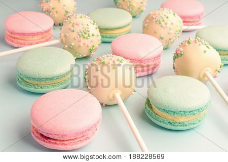 Close-up of macaroons mixed with cake pops with icing on sticks on blue background