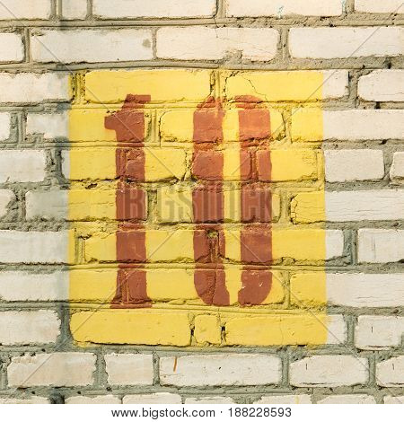 Stencil figure ten red in a yellow square on a white brick wall
