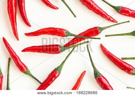 red hot chili peppers, popular spices concept - closeup on beautiful red hot chili peppers isolated on white background, green tails, collage of freely lying peppers, top view, flat lay