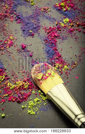 Make-up brush on texture of colorful make-up powder. Flat lay. Top view