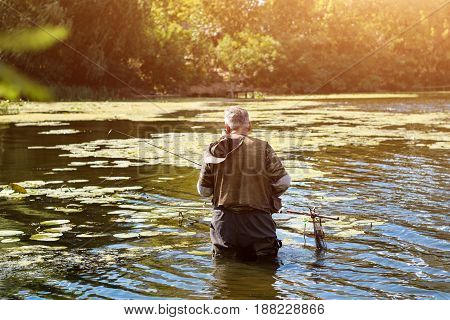 Old fisherman fishing in a lake or river with a fishing rod on a sunny day. Man standing in the water.