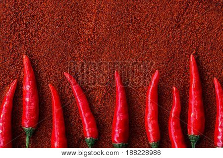red hot chili peppers, popular spices concept - sharp composition of nine pods of red chili peppers on a brown background from a powder of ground hot pepper, flat lay, free space for text