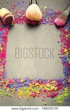 Make-up frame background with brushes. Colorful make-up powder template with copy space