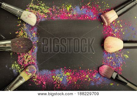 Colorful make-up frame template with make-up brushes on black chalkboard background. Flat lay. Top view