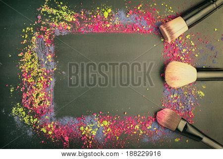 Top view of make-up frame with professional brushes on black background. Flat lay