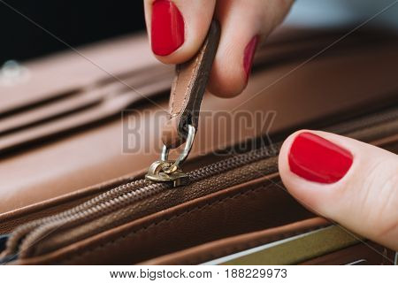 The girl unbuttoned her leather wallet in search of coins
