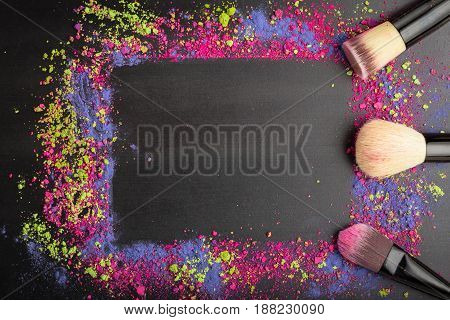 Makeup frame template with brushes. Colorful makeup powder on black background as template. Flat lay. Top view