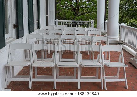 Rows of White Folding Chairs on Brick Patio waiting for guests