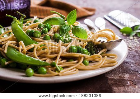 Dark spaghetti with green peas and parmesan. Selective focus.