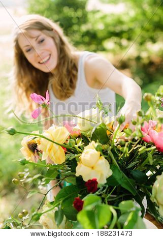 wedding, decoration, floral design, applied arts concept - in foreground beautiful bouquet composed of yellow roses, pink peonies and avalanches. in background smiling woman fixing few flowers