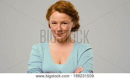 Mid aged actress showing emotions of cunning. Actress in studio shows the tricky emotions. Close-up portrait of an actrees in light blue jumper. Actress with red hair shows the emotion of cunning.