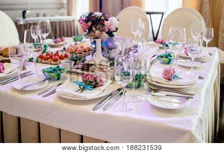 Pink Roses With Blue Ribbon On White Empty Plate With White Napkin On Dinner Table In Blur. Table Se