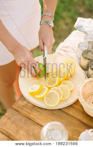 food, health, lifestyle, vegetarianism, cooking, nature concept - woman's hands with bright orange manicure, silver bracelet and wrist watch slice lemon and lime on white plate