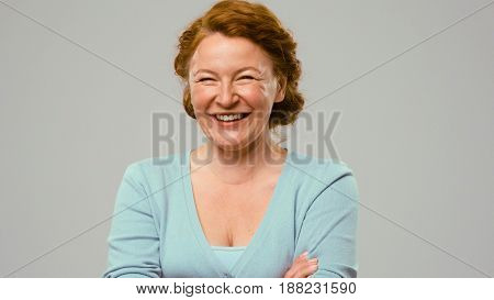 Mid aged actress showing emotions of joy. Actress in studio shows the emotion of joy. Close up portrait of an actrees in light blue jumper. Actress with curly red hair shows the emotion of joy