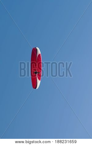 Colorful hang glider in sky over blue.