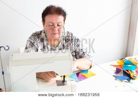 patchwork and quilting at the workshop of a tailor woman on white background - woman with glasses sews on the sewing machine scraps of colorful fabrics for patchworking