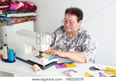 needlework and quilting in the workshop of a tailor - older woman with glasses works at a desk with a sewing machine and thread, fabrics, needles, pins, buttons, scissors, rotary cutters