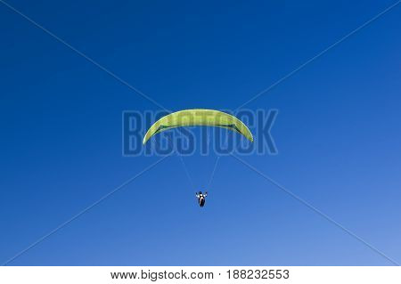 Colorful hang glider in sky over the blue. Sardinia west coast.