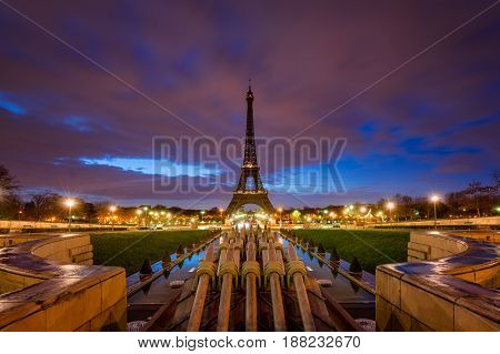 Eiffel Tower at dawn with clouds and city lights from Trocadero Paris France
