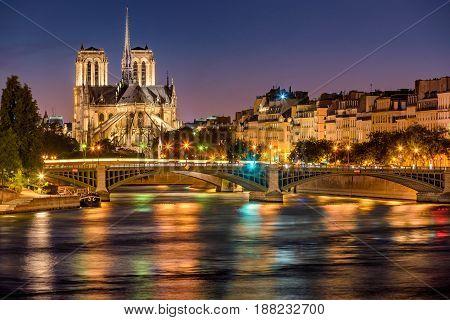 Notre Dame de Paris Cathedral Seine River and the Sully Bridge at twilight. Summer evening on Ile Saint Louis 4th Arrondissement in Paris. France