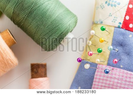 needlework, quilting, sewing and tailoring concept - colorful cute stitched pincushion with beautiful pins, tools closeup on white desk, green, pink and peach thread spools, flat lay, top view