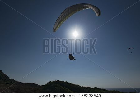 Sport paragliding in backlight with blue sky background and sun in front. Silohuette.